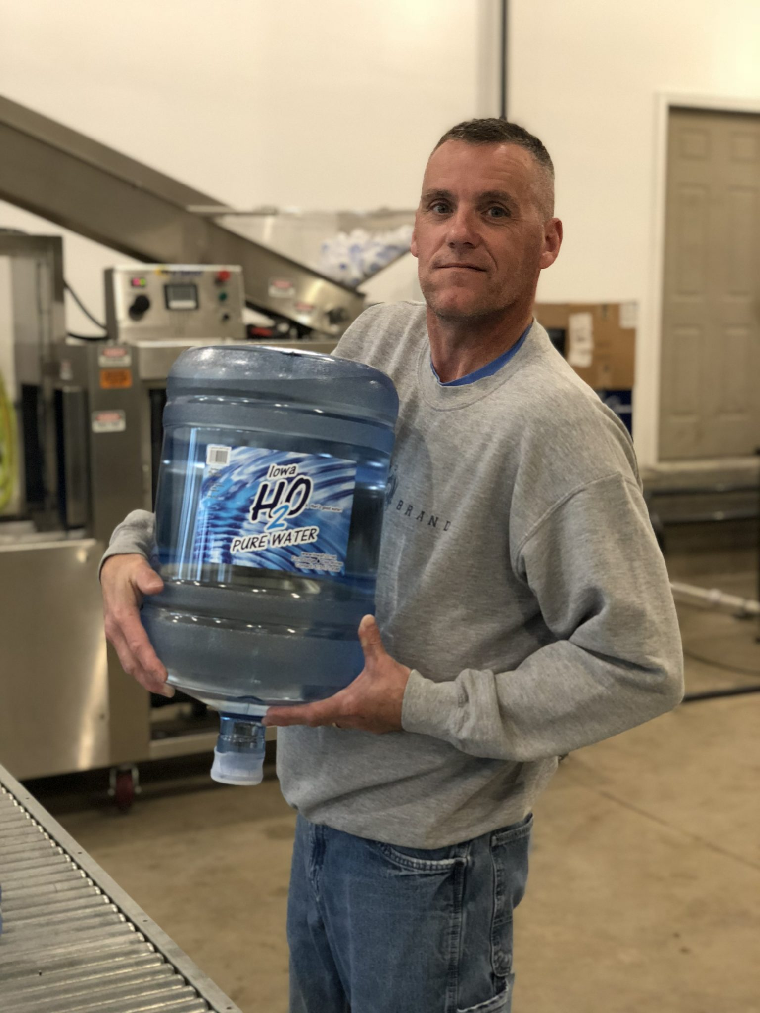 John Miles, certified water specialist holding a 5 gallon bottle